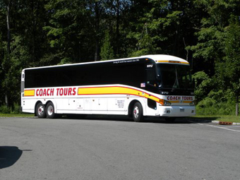 White with red and yellow trim Coach Tours bus in parking lot set in front of green trees can send you on the best motorcoach bus tours