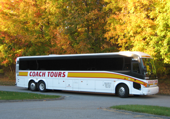 Coach Tours white bus with yellow and red trim in a parking lot with fall foliage in the background
