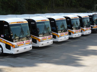 A fleet of 5 white, red and yellow, Coach Tours motorcoach buses in a parking lot ready for travel in the Northeast