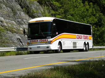 Luxury motorcoach is traveling down highway in the country.