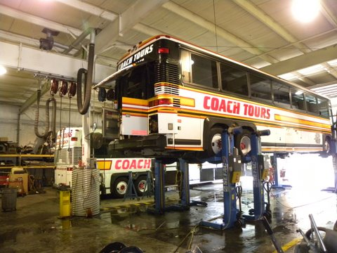 Tour bus on a lift in a maintainence facility.