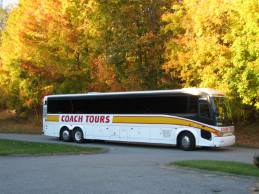 Tour bus driving through the fall foliage.