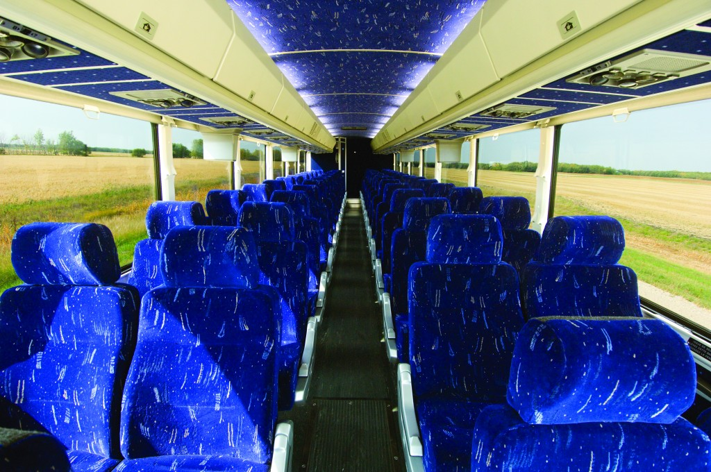 Luxurious blue seats in the interior of a motorcoach bus.