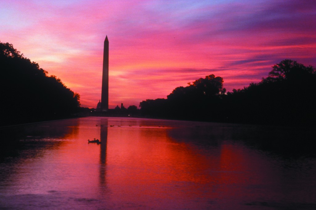 The Washington Monument and reflecting pool under a red sunset.