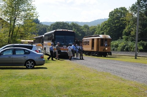 Coach Tours motor coach passengers arrive at a scenic rural location.