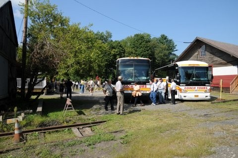 Luxurious charter tour buses arrival at a rustic Northeast tourist location.