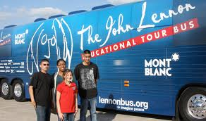 The blue John Lennon Educational Bus with students posing along side.