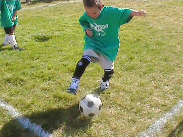 Little boy in green uniform kicking a soccer ball at summer camp.