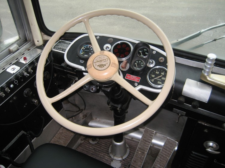 White vintage steering wheel and controls of a 1964 MCI Greyhound bus.