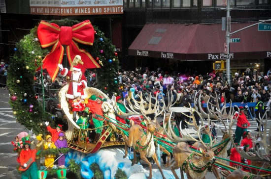 Santa standing up in his gold sleigh during Macy's Christmas parade in NYC.