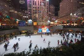 Christmastime skating at Rockefeller Center in NYC at night with the surrounding buildings decorated and lit up.