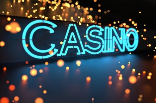 Casino sign in blue neon on black background with yellow and orange glowing lights.