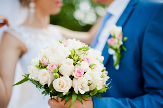Bouquet of flowers in the foreground of two newlyweds.