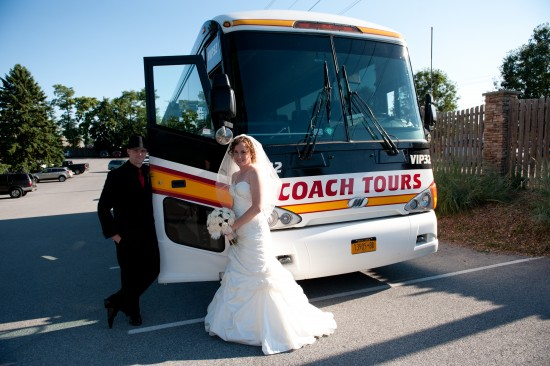 Bride & groom getting ready to enter large Coach Tours charter bus.