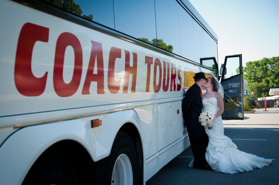 Bride & groom sharing a kiss in front of a Coach Tours large white charter bus.