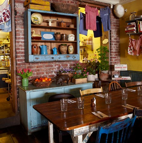 An interior photo of Miss Lucy's Kitchen restaurant with rustic colorful decor, brick walls and antique tables.