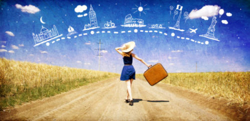 A girl in a blue dress and a brown hat walking down a dirt road in the middle of a cornfield looking carefree & carrying a brown suitcase.