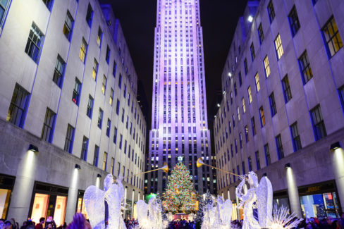 Rockefeller Center in NYC during Christmas time with the buildings, angel sculptures, and tree.