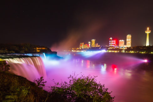 A colorful view of Niagara Falls in night lights with casinos and hotels in the background.
