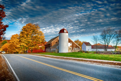 A country farm stone barn with large white silo along a two lane country road within the beautiful fall foilage.