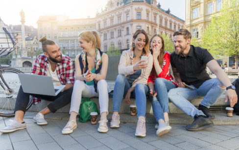 Millennials sitting around a fountain in a city looking at their smart phones and computers while laughing and having fun with their friends.