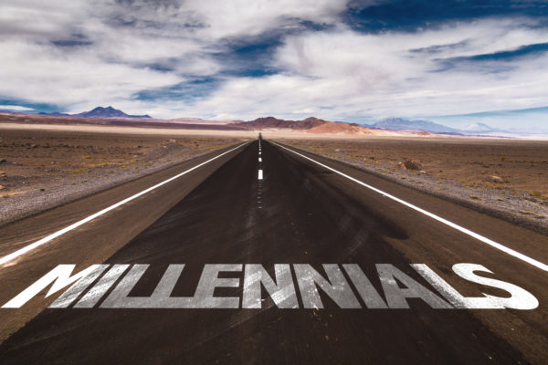 Millennials written in large white letters on an open desert road.