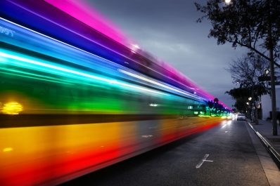 rainbow-like swirl of colors follows a futuristic bus on a highway.